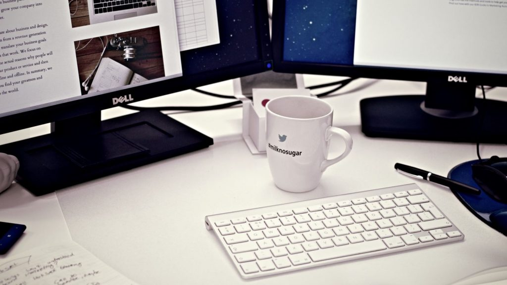 two computer monitors and a coffee mug on a desktop for blogging