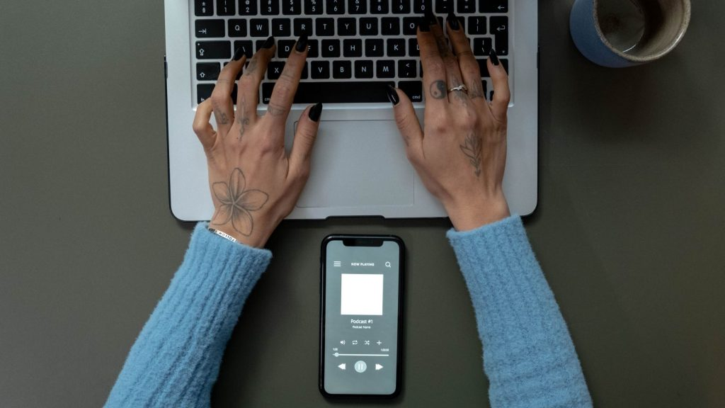 graphic designer typing while listening to a podcast