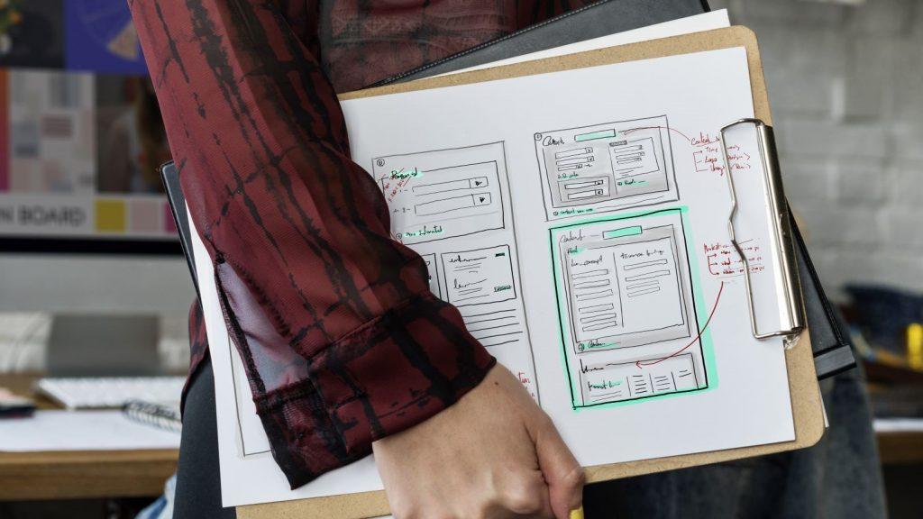 women holding a sketch of a web design